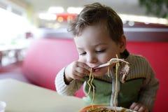 Criança que come os espaguetes Fotografia de Stock Royalty Free