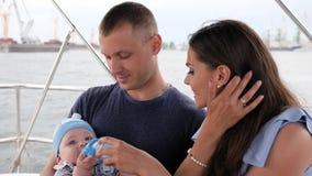 A criança que come seu primeiro frutifica nas mãos paizinho, família com o bebê em férias, pais e crianças no mar, par feliz dent vídeos de arquivo
