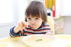 Criança que come a sopa de creme vegetal Nutrição saudável Imagens de Stock