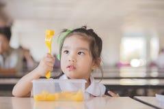 Criança que come um fruto, lotes do fruto fresco na tabela na parte dianteira como após a escola fotografia de stock