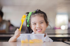 Criança que come um fruto, lotes do fruto fresco na tabela na parte dianteira como após a escola imagens de stock royalty free