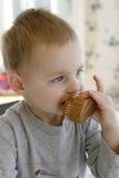 Criança que come um queque fotografia de stock royalty free