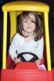 Criança que conduz o carro do brinquedo Fotografia de Stock Royalty Free