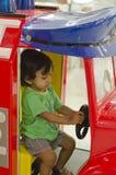Criança que conduz o carro do brinquedo da roda de direcção Imagens de Stock Royalty Free