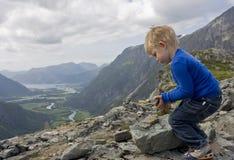 Criança que constrói um monte de pedras Fotografia de Stock Royalty Free