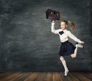 Criança que corre à escola, criança que salta, quadro-negro da menina da sala de aula fotos de stock