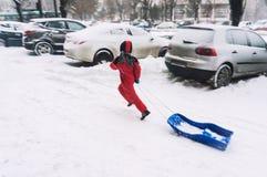 Criança que corre com pequeno trenó Fotografia de Stock Royalty Free