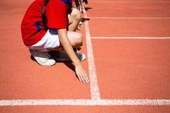 Criança que corre na trilha no estádio Fotos de Stock
