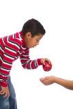 Criança que dá Apple à pessoa na necessidade Foto de Stock Royalty Free