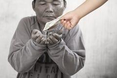 Criança que dá o dinheiro ao pedinte fotografia de stock