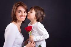 Criança que dá a rosa lindo do vermelho a sua mamã Imagem de Stock
