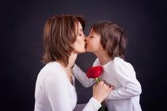 Criança que dá a rosa lindo do vermelho a sua mamã Fotografia de Stock Royalty Free
