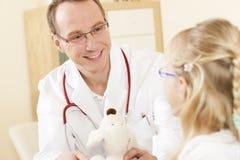 Criança que dá um brinquedo macio ao doutor Imagens de Stock Royalty Free