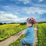 Criança que dá um ciclo em um prado da mola fotografia de stock royalty free