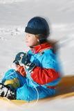 Criança que desliza do monte Fotografia de Stock