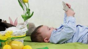 Criança que encontra-se com smartphone, desenhos animados de observação do rapaz pequeno vídeos de arquivo