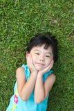 Criança que encontra-se na grama Fotografia de Stock Royalty Free