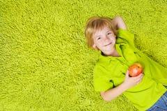 Criança que encontra-se no tapete verde, prendendo a maçã Fotografia de Stock Royalty Free