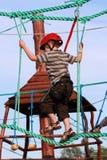 Criança que escala no campo de jogos da aventura Fotografia de Stock Royalty Free