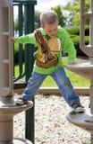 Criança que escala no equipamento do campo de jogos Fotografia de Stock