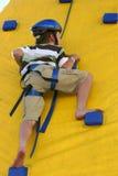 Criança que escala uma parede de escalada Fotografia de Stock