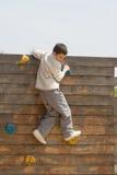 Criança que escala uma parede de madeira imagem de stock royalty free