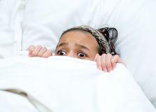 Criança que esconde atrás do cobertor ao prestar atenção ao filme Imagens de Stock Royalty Free