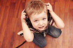 Criança que escuta uma música nos fones de ouvido Fotografia de Stock Royalty Free