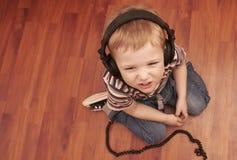Criança que escuta uma música nos fones de ouvido Imagem de Stock Royalty Free