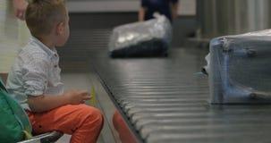 Criança que espera na área de reivindicação de bagagem filme