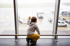 Criança que espera no terminal de aeroporto imagens de stock