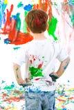 Criança que está para trás e que admira sua pintura Fotos de Stock