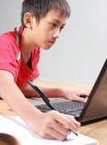 Criança que estuda com livros e portátil Fotos de Stock