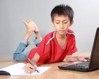 Criança que estuda com livros e portátil Fotografia de Stock Royalty Free