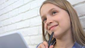 Criança que estuda na tabuleta, menina que escreve para a turma escolar, aprendendo fazendo trabalhos de casa fotografia de stock royalty free
