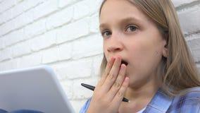 Criança que estuda na tabuleta, menina que escreve para a turma escolar, aprendendo fazendo trabalhos de casa fotografia de stock