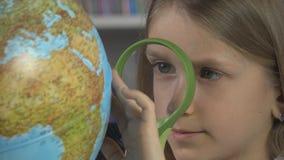 Criança que estuda o globo da terra na turma escolar, menina que aprende, criança na biblioteca imagens de stock royalty free