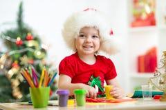 Criança que faz a árvore de Natal do plasticine Fotografia de Stock