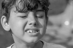 Criança que faz expressões faciais estranhas imagens de stock