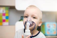 Criança que faz a inalação com máscara em sua cara imagem de stock royalty free