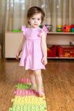 Criança que faz massagens seus pés na esteira médica Imagem de Stock Royalty Free