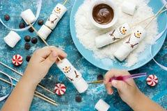 A criança que faz o marshmallow do boneco de neve estala, composição da cozinha para w Imagens de Stock