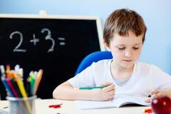 Criança que faz seus trabalhos de casa Foto de Stock Royalty Free
