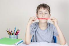 Criança que faz trabalhos de casa na tabela e no pensamento ou no sonho imagens de stock