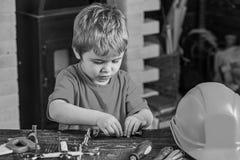 Criança que fixa dois detalhes do metal Menino concentrado que trabalha com parafusos de parafuso Criança em idade pré-escolar qu imagem de stock