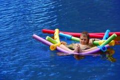 Criança que flutua com macarronetes fotografia de stock
