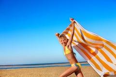 Criança que funciona na praia com toalha Imagem de Stock Royalty Free