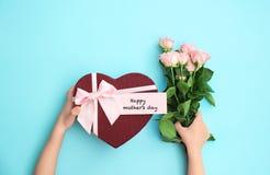 Criança que guarda a caixa de presente e as flores para o dia do ` s da mãe Foto de Stock