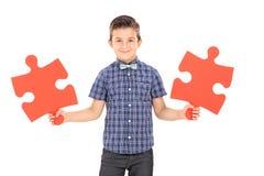 Criança que guarda duas partes de um enigma Fotos de Stock Royalty Free
