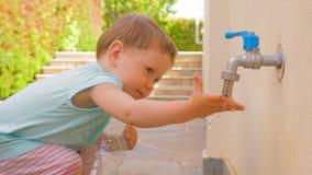 Criança que guarda a garrafa plástica vazia perto da torneira Fundo privado do jardim de infância Criança em idade pré-escolar qu video estoque